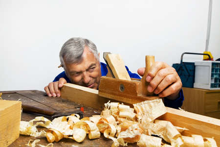 hobbyist: a carpenter with a planer and wood shavings in the workshop.