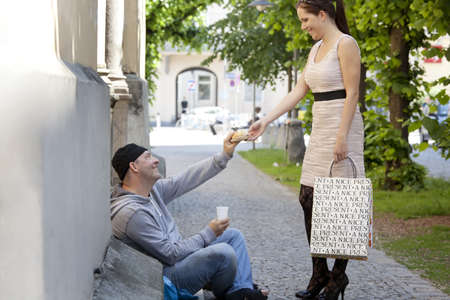 hartz 4: a rich young woman gives food to a beggar. Stock Photo