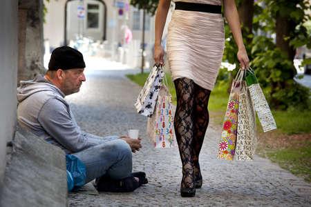 rijke vrouw: een bedelaar en een rijke vrouw tijdens het winkelen met boodschappentassen Stockfoto