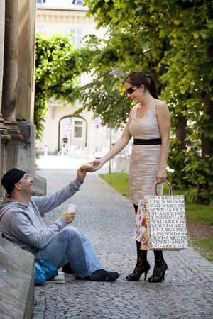 rich life: a rich young woman gives food to a beggar. Stock Photo