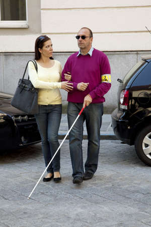 a blind: a young woman helps a blind man on the street