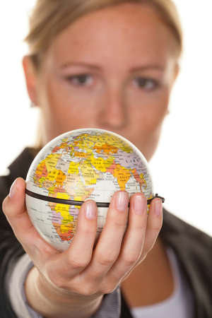 long haul journey: a young woman holding a globe in his hand. photo icon for tourism and travel environment