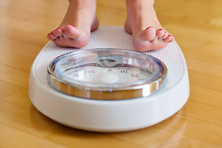 decreasing: the feet of a woman standing on bathroom scales to turn
