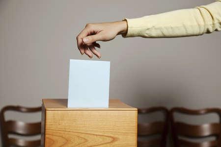 democracia: una mujer joven con un votante en las urnas. votar en una democracia