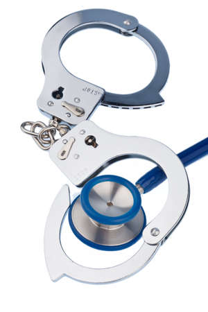 bribes: handcuffs and a stethoscope lying on a white background.