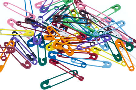 many colorful safety pin lying on a white background photo