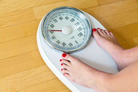 thinness: the feet of a woman standing on bathroom scales to turn
