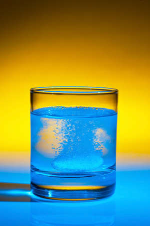 an effervescent tablet dissolves in a glass of water on Stock Photo - 11275457