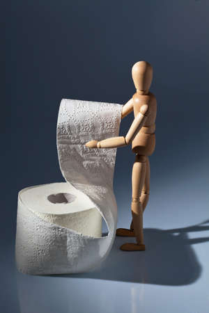 intestinal problems: a wooden figure and a roll of toilet paper.