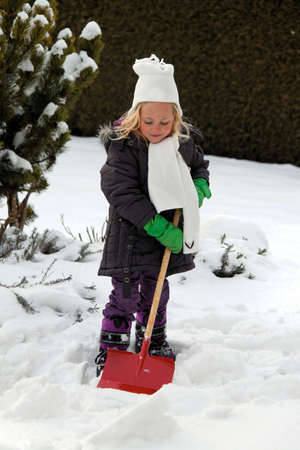 homeowners: small girl with snow shovel snow shovel in the winter