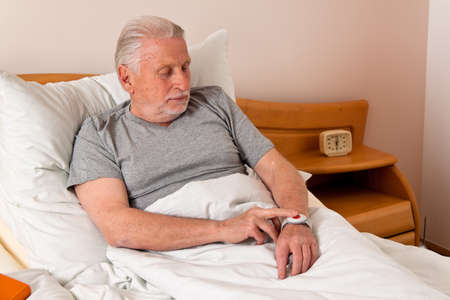 emergency call: rufhilfe with a senior emergency phone in bed Stock Photo