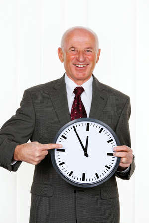 constraints: a manager keeps a clock. on the dial, it is 11:55 Stock Photo