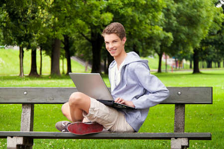 ordinateur: a teenager with laptop outdoors. sitting in the park mobile internet Stock Photo