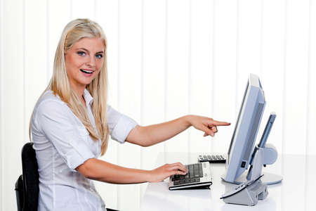 freelancers: young woman with a computer and monitor in the office