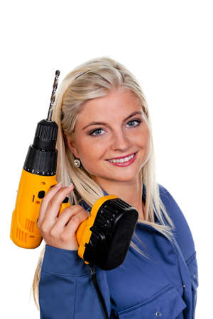 young woman in blue work clothes with a drill. photo