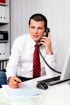 young businessman with phone sitting at a desk Stock Photo - 11276279