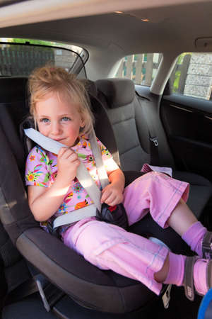 small child sitting in the car seat in the car photo