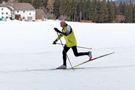 Senior im Winter auf Schnee zu Langlauf mit Skiern zu �berqueren Lizenzfreie Bilder
