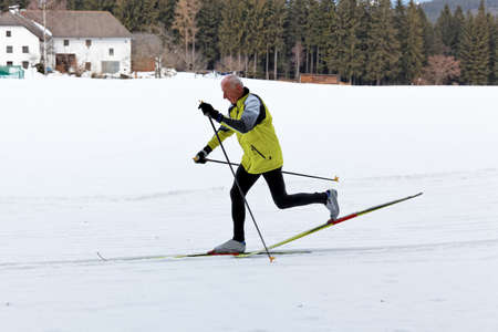 senior in winter on snow to cross country skiing with skis photo