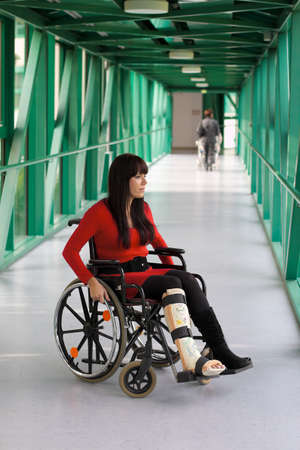 skiing accident: young woman with leg in plaster and wheelchair in the hospital Stock Photo
