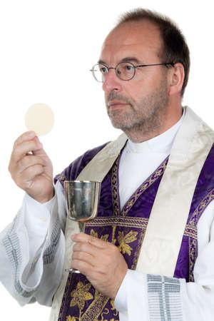 sacerdote: un sacerdote católico con un cáliz y la patena en la sagrada comunión