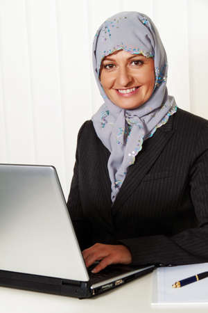 migrant: photo icon islam. muslim woman wearing a headscarf in the office at work. Stock Photo