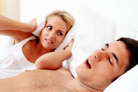 snore: couple in scvhlafzimmer. husband snores loud and unpleasant. Stock Photo