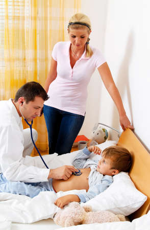 bedridden: a doctor at home visits. examines a sick child.