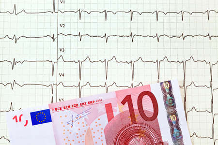 a ten-euro note is on an ecg curve. medical expenses and\ payment