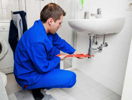 sink drain: a plumber repairing a broken sink in bathroom Stock Photo