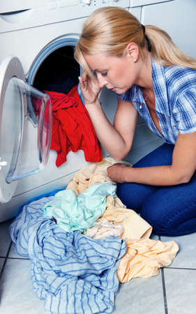 a young housewife with washing machine and clothes. washday. photo