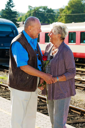 mature vital elderly couple at the train station. travel on holiday photo