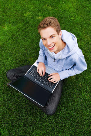 a teenager with laptop outdoors. sitting in the park mobile internet Stock Photo - 11275635