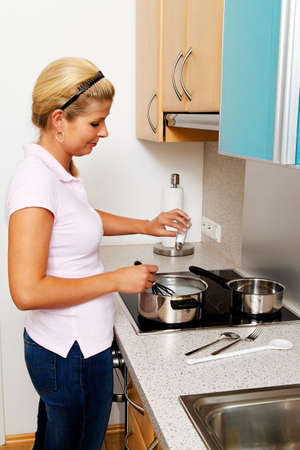peoplesoft: a woman in the kitchen while cooking with electric stove