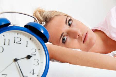 insomnio: reloj con el sue�o por la noche. mujer no puede dormir.