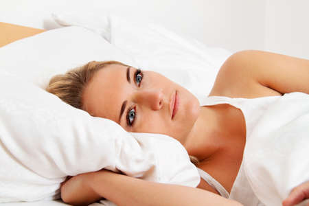 restful: a young woman lies awake in bed. sleepless and thoughtful.