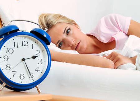 insomnio: reloj con el sue�o por la noche. la mujer no puede dormir.