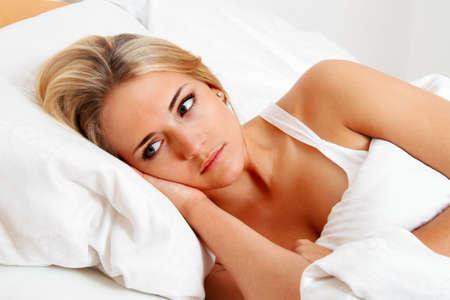 akkoord: een jonge vrouw ligt wakker in bed. slapeloze en attent.