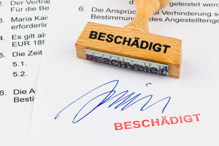 deficient: a stamp made of wood lying on a document. damaged inscription Stock Photo