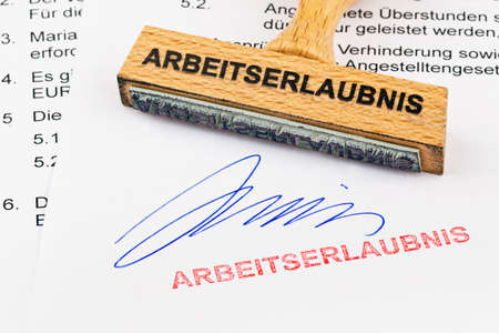 naturalization: a stamp made of wood lying on a document. inscription work permit Stock Photo