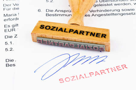 degrading: a stamp made of wood lying on a document. marked social partners