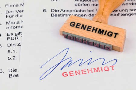permission: a stamp made of wood lying on a document. approved inscription