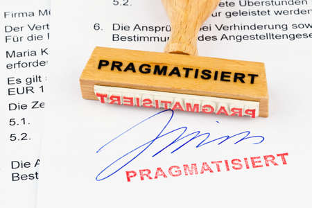 public service: a stamp made of wood lying on a document. inscription pragmatized Stock Photo