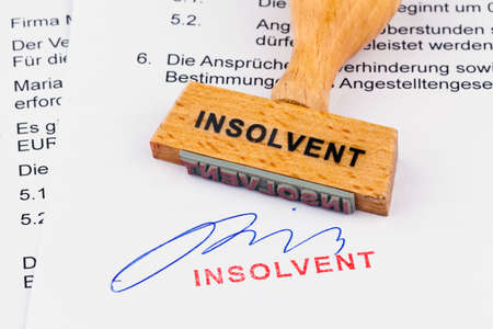 insolvency: a stamp made of wood lying on a document. inscription insolvent
