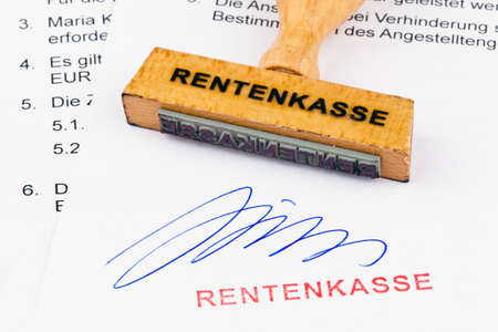 incapacitated: a stamp made of wood lying on a document. inscription retirement fund