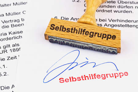 therapie: a stamp made of wood lying on a document. labeled self-help group