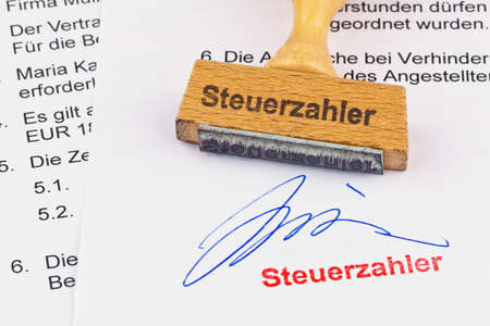 a stamp made of wood lying on a document. inscription taxpayers photo