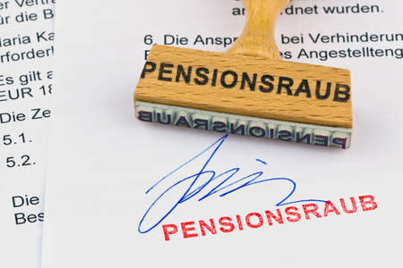 degrading: a stamp made of wood lying on a document. inscription pension robbery Stock Photo