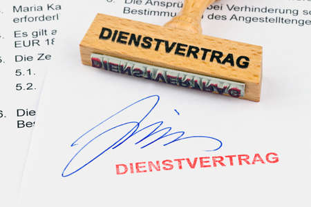 arbeitsrecht: a stamp made of wood lying on a document. inscription service contract