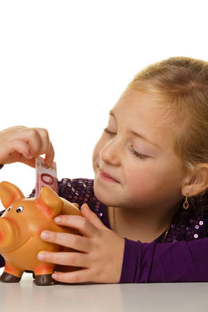 clavados: un niño pequeño pone un billete de un dólar en una alcancía. euros farsa. Foto de archivo